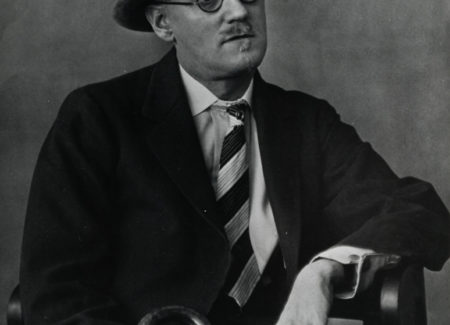 black and white photograph of man in suit and hat and round glasses holding cane seated in chair