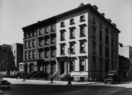 black and white photograph of multi-story row houses on city street corner with antique cars on street