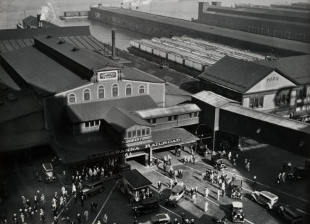black and white aerial image of busy parking lot in front of Lackawanna Railroad and Hoboken Ferry station