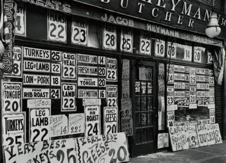 black-and-white photograph of butcher storefront covered in signs