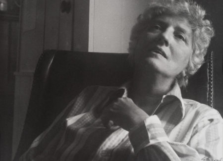 black and white photograph of woman in white striped shirt leaning back in chair