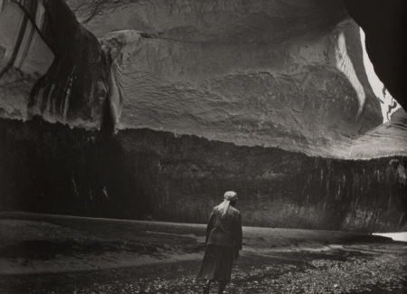 black and white photograph of person wearing head scarf walking alongside water inside cave