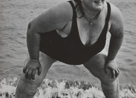 black and white photograph of woman in black bathing suit with hands on knees in front of ocean