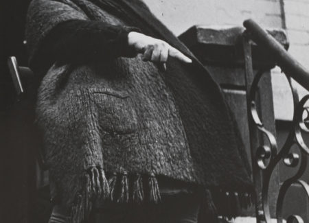 older woman in heavy coat and scarf on house stoop pointing at something out of frame, black-and-white photograph