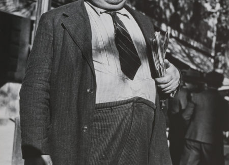 man in suit with short tie and flat cap standing on street with eyes half-closed, black-and-white photograph