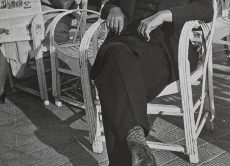 man in suit leaning back with eyes closed in cafe chair, black and white photograph