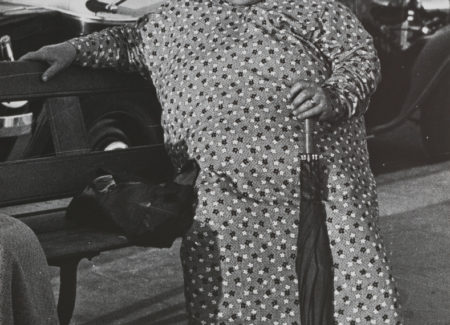 woman in long loose dress, white sneakers and patterned wide-brimmed hat holding umbrella and seated on park bench - black and white photograph
