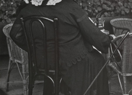 woman in black dress and wide brimmed hat sitting in cafe chair, seen from behind, black and white photograph