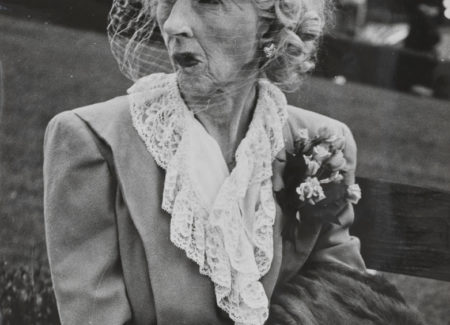 older woman in suit with frilly shirt color, veiled hat with flowers, corsage with fur coat in lap and puckered lips seated on park bench, black and white photograph