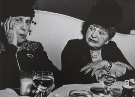 two women wearing black with black hats seated at restaurant table in conversation, black and white photograph