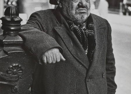 older man in wool overcoat and fedora hat leaning on banister on city street, black and white photograph