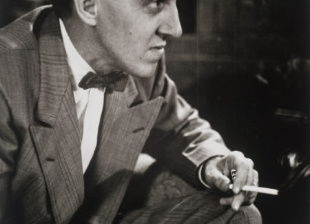 man in suit and bow-tie seen from side sitting and smoking cigarette