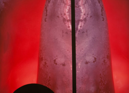 abstract image with red lit background, purple cylindrical object in center bisected by black vertical line and black semi-circular shape in lower left