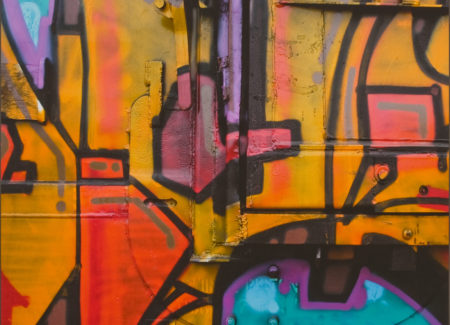 close up of colorful yellow, red, blue and purple graffiti