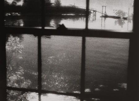 lake, cottage and dock seen through paned window, black and white photograph