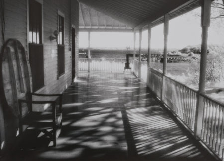 view down front porch with pier and ocean in background