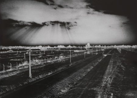 negative image of railroad tracks and field with sun streaming through clouds