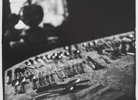 black and white photograph of silverware on lace tablecloth
