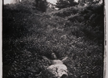 shirtless man lying in low-growing plants on hill, black and white photograph