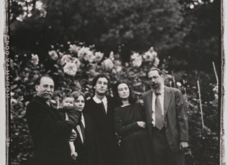 black and white family photograph of three men, a woman and two children in garden