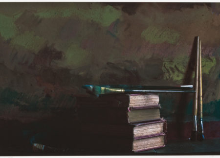 paint brushes on top of and beside stack of books in front of abstractly painted canvas in dark, muted colors