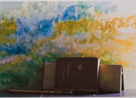 books stacked in front of abstract watercolor painted canvas in blues, yellow and greens with paint brush in foreground