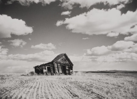 dilapitated wooden barn in field, black and white photograph
