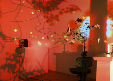 color photograph of wire sculpture creating shadows on wall when light by red light