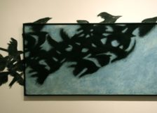 black birds flying on wall and through blue canvas