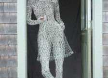 wound chicken-wire sculpture of woman leaning in door frame, wearing red shoes