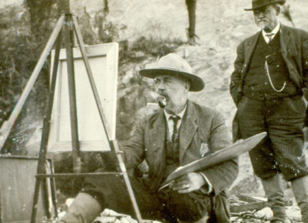 Sepia photograph of John Calvin Stevens smoking a pipe and painting at an easel outdoors
