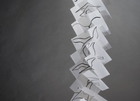 black and white photograph of book pages suspended and descending, with pages in shape of and depicting bird in flight