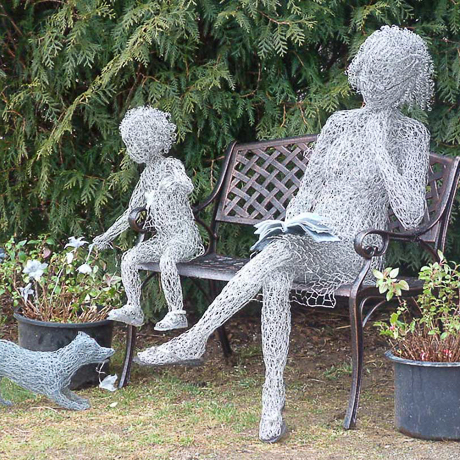 wire sculpture of woman and child seated on a bench with small dog