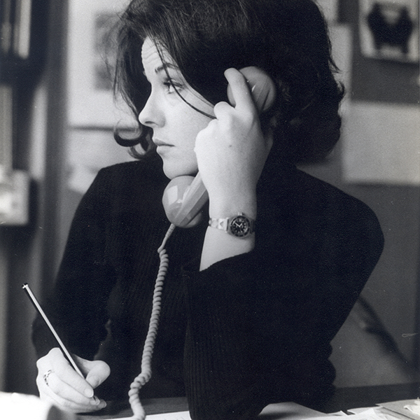 lack and white photograph of Perdita Huston on the phone taking notes
