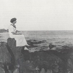 Sarah Orne Jewett seated on a rock in front of the ocean looking out to sea.