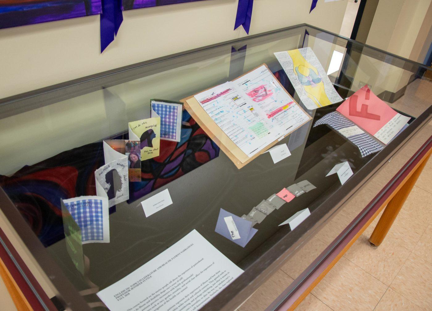 exhibit case featuring student art books.