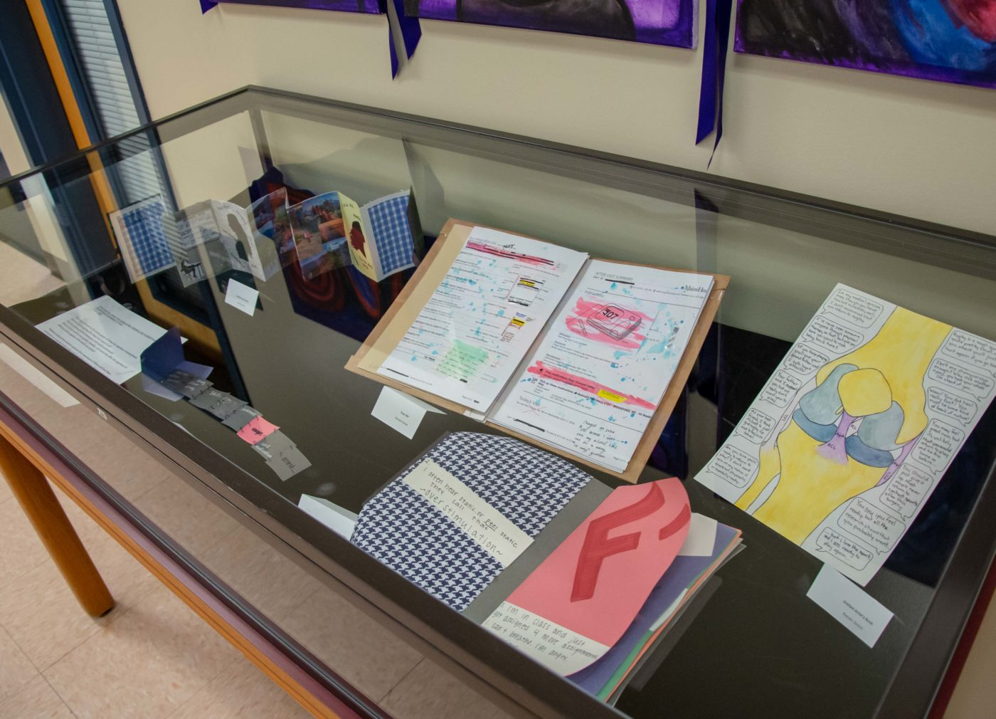 Detail of student artbook pages in exhibit case.
