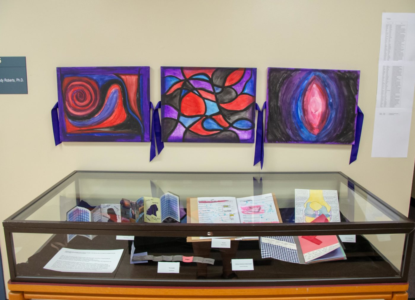 exhibit wall featuring colorful artwork in swirling abstract shapes above exhibit case with open art books displayed.