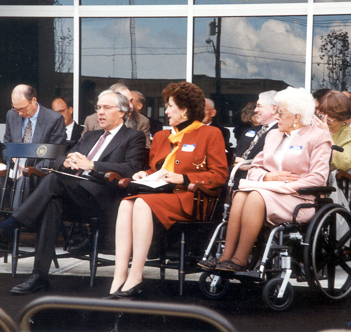 Huston seated on stage with small group