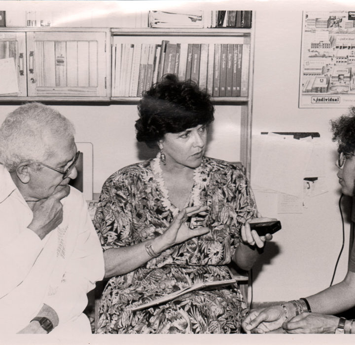 black-and-white image of Huston seated, speaking to an older man and young woman in Egypt, 1990.