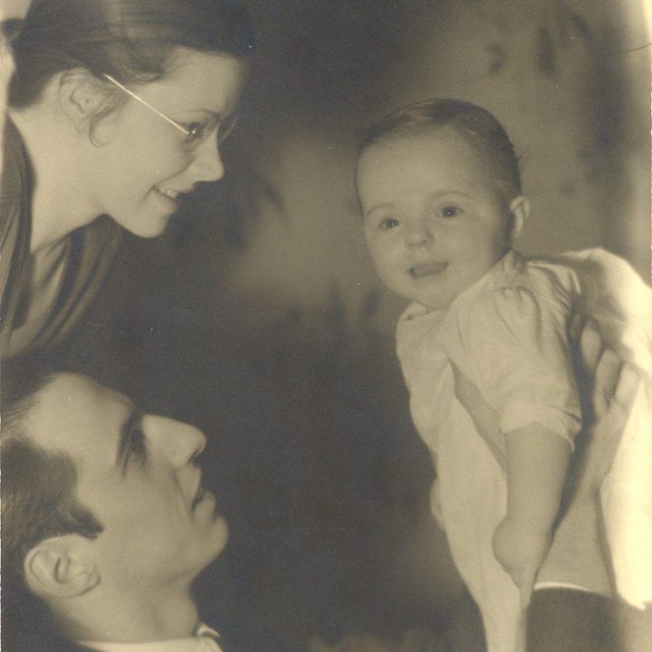 1936 black-and-white image of Perdita Huston as a smiling baby held up by father with mother leaning in to frame