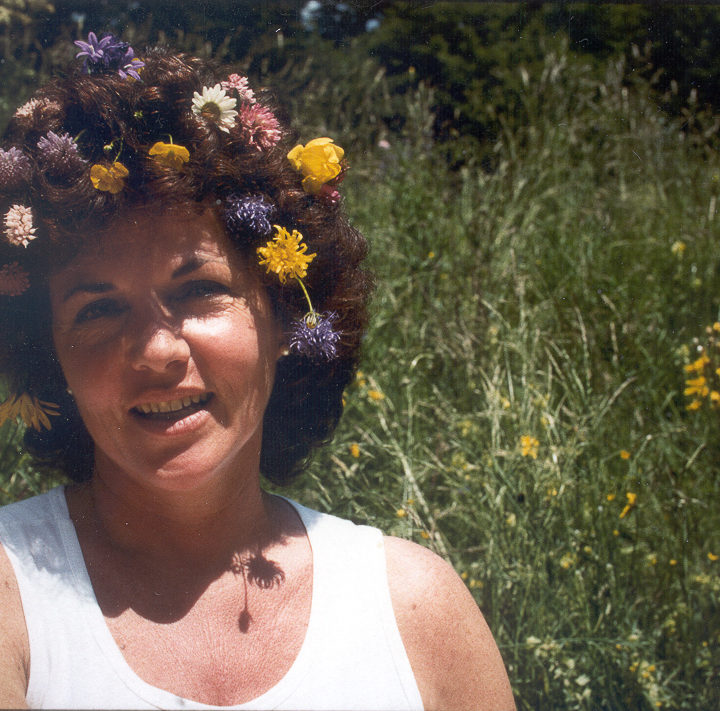 Huston sitting in a field with many flowers in hair, 1987