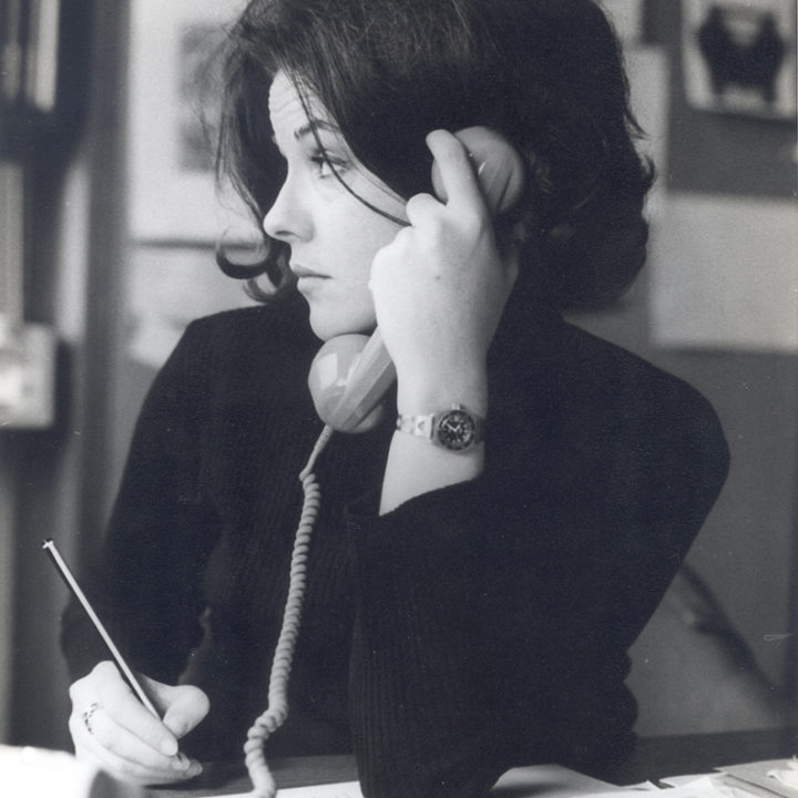 black-and-white photograph of Huston holding a telephone in one hand, pencil in other, looking sideways