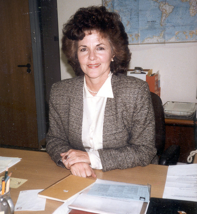 Huston seated at desk in front of world map, taken 1990