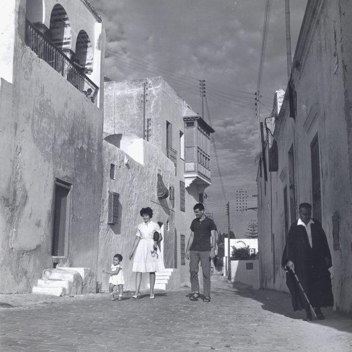 black and white photo of Huston, husband and daughter on the streets of Tunis, 1959
