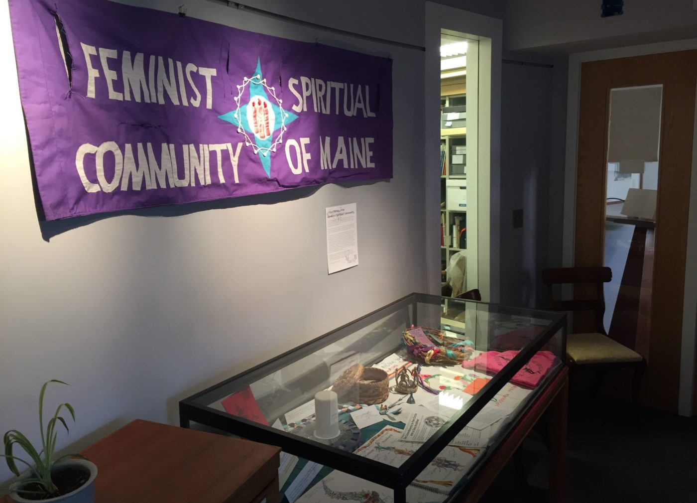 Feminist Spiritual Community banner and exhibit case in Maine Women Writers Collection space.