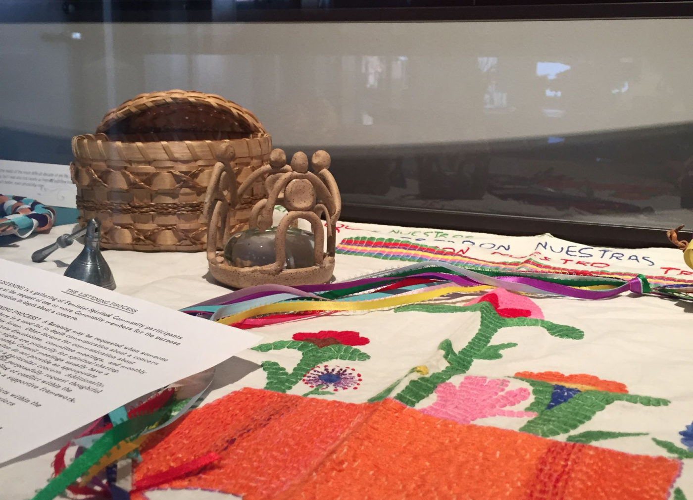 Detail of embroidered flowers growing from tree stump, female figure candle holder, a page, and a basket from exhibit case.