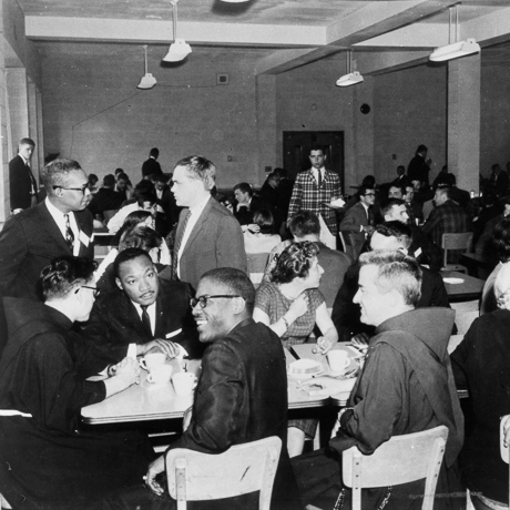 Martin Luther King Jr. seated in busy dining hall