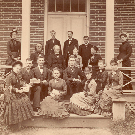 sepia image of men and women seated on porch