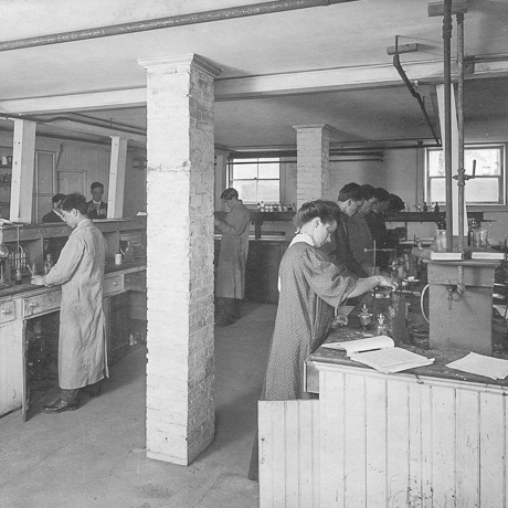 historical photograph of men and women working in lab